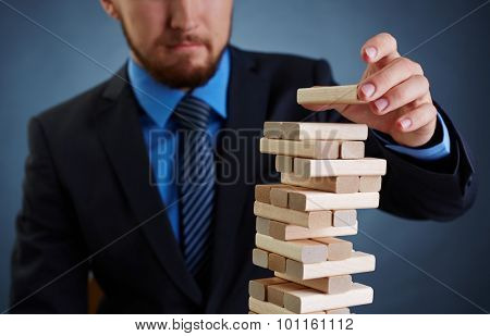 Concept of financial instability: businessman putting small wooden block on top of tower