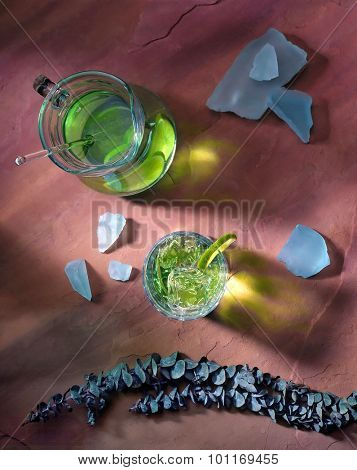 High angle shot of a pitcher of lime ade on a red sandstone background.