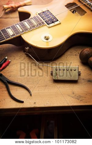 Electric guitar repair. Vintage electric guitar on a guitar repair shop work bench. gold color. shallow depth of view, intentionally shot with low key shadows.