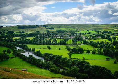 Meandering River Making Its Way Through Lush Green Rural Farmland In The Warm Early Sunlight. poster