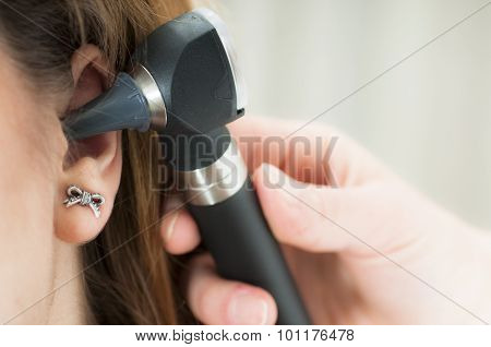 Young Woman Doctor Monitors The Patient's Ear With Otoscope