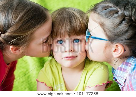 Embarrassed girl looking at camera. Toddler girl being kissed by two sisters. poster