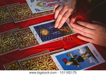 Fortune teller using tarot cards on red table
