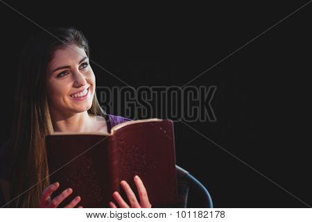 Woman praying with her bible on black background