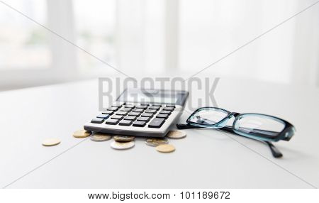 busines, finance, money and bookkeeping concept - calculator, eyeglasses and euro coins on office table