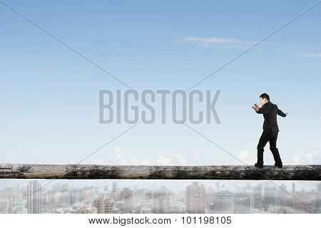 Businessman Balancing On Tree Trunk High In The Sky