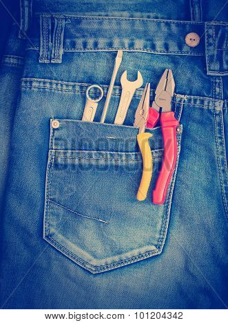 Several tools on a denim workers pocket.