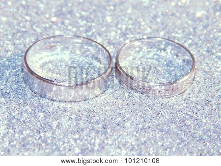 Two wedding rings of white gold on silver glitter sparkle