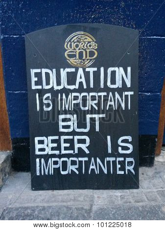 EDINBURGH, SCOTLAND, UK - CIRCA AUGUST 2015: Education is important but beer is importanter, funny pun wooden sign label at the entrance of a pub