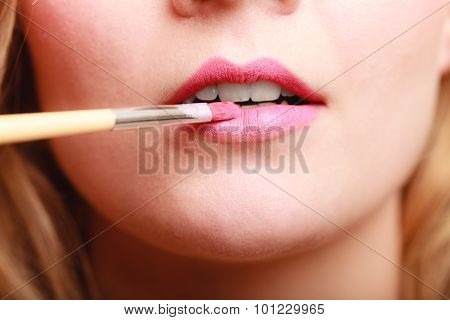 Cosmetic beauty procedures and makeover concept. Closeup part of woman face pink lips. Make-up artist applying lipstick with accessories tools. poster