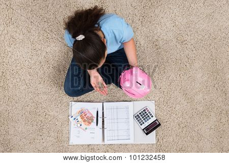 Woman Sitting On Carpet With Invoices And Money Inserting Coin In Piggybank poster