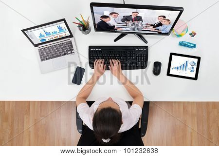 Businesswoman Videoconferencing With Co-workers On Computers