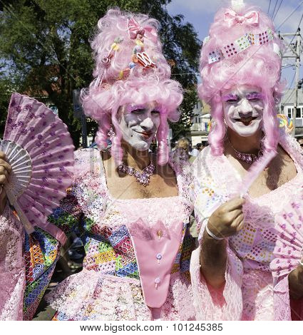 Drag queens in pink wigs walking in the 37th Annual Provincetown Carnival Parade in Provincetown, MA