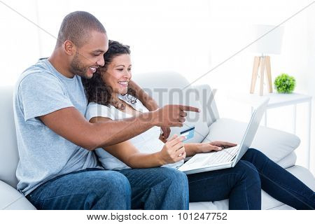 Couple enjoying online shopping sitting on sofa at home