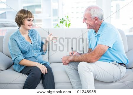 Happy pregnant woman talking to gynaecologist while sitting on sofa at home