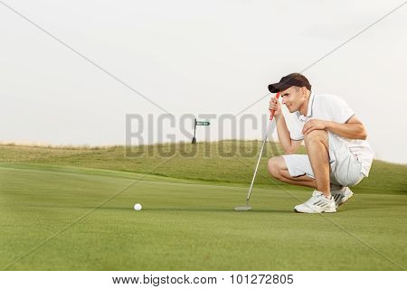 Golfer assessing his options to putt the ball