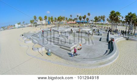 LOS ANGELES - OCT 19, 2014: Young people ride on skateboards by Venice Beach Skate Park at sunny day. Aerial view. Skatepark total area is about 1500 sq.m.