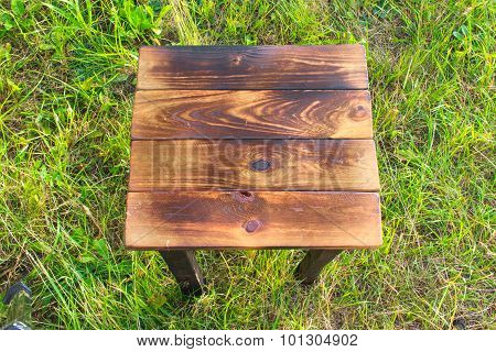 Small burnt wood table on grass