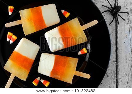 Halloween candy corn ice pops on black plate