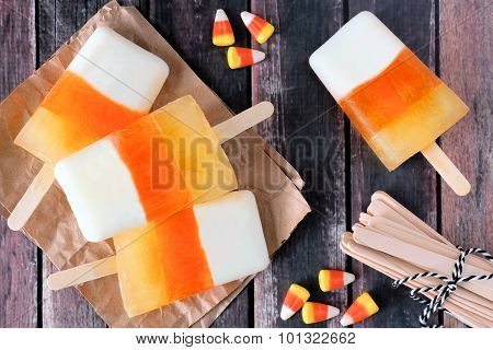 Halloween candy corn ice pops on rustic wood background