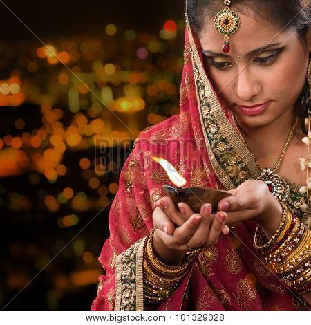 Indian female in traditional sari lighting oil lamp and celebrating Diwali or deepavali, fesitval of lights at temple. Woman hands holding oil lamp, beautiful lights bokeh background.