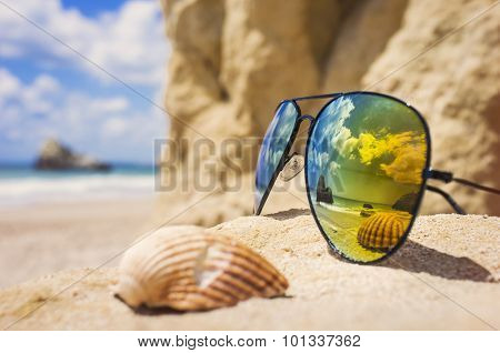 Poly-color sunglasses, reflecting the ocean and a shell on a sandy, tropical beach