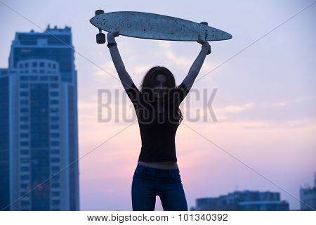 Stylish girl in jeans holding aloft longboard