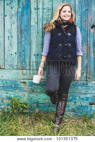 Autumn woman holding coffee mug. Fall concept of young woman enjoying fredom in city park.