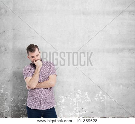 Young Man In Casual Shirt Holds His Chin And Thinks About The Best Solution Of The Problem. The Conc