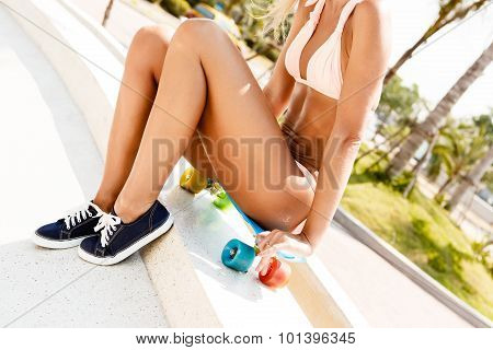 Skinny sporty tanned girl in bikini sitting on her blue penny board longboard with multi colored wheels poster
