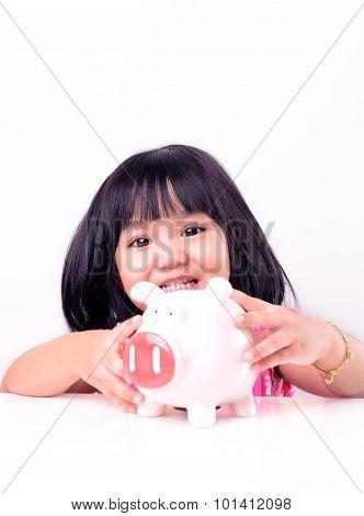 Little girl holding piggy bank