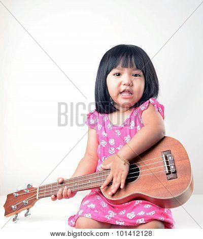 Little girl playing ukulele