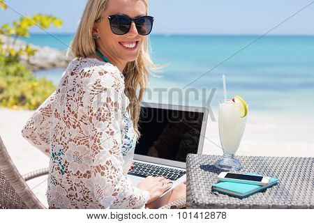 Successful business woman working with computer on the beach