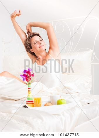Charming woman having breakfast in bed