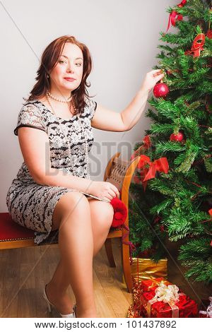 Middleage woman decorates Christmas tree