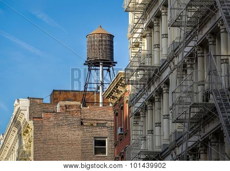 Cast iron facades of Soho loft buildings and rooftop wooden water tank in Downtown Manhattan New York City poster