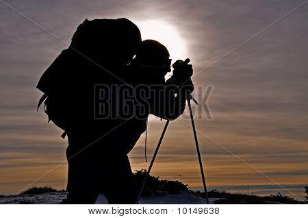 The tourist photographs on an evening hillside.