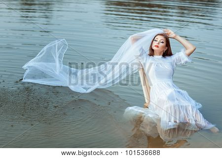 Bride Sitting In A Lake, Her Veil Wet.