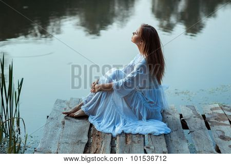 Girl Sitting On A Wooden Pier And Dreams.