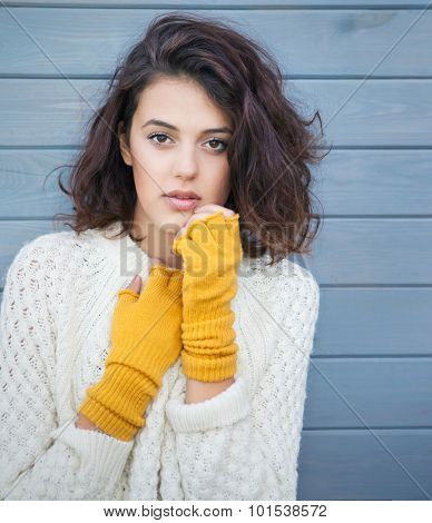 Beautiful natural young brunette woman wearing knitted sweater and gloves. Fall and winter fashion concept.