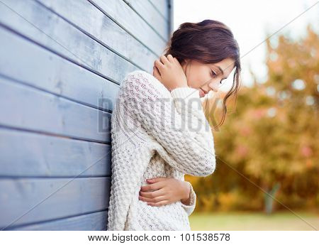Beautiful natural young brunette woman wearing knitted sweater by the house. Fall and winter fashion concept.