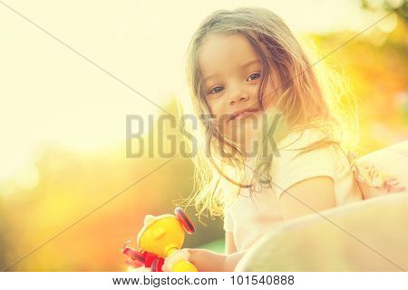 Smiling little girl with toy in hands. Portrait in nature with warm sunlight.