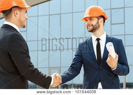 Handshake of two handsome colleagues outdoors