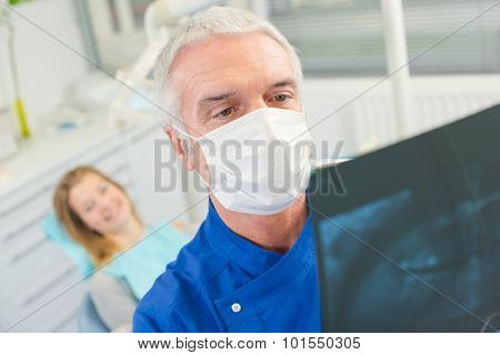 Dentist checking x-ray before drilling