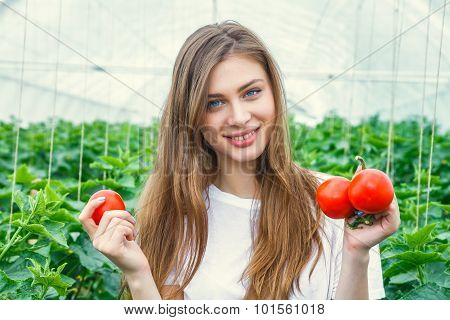 Beautiful girl farmer holding tomato
