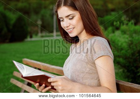 Attractive girl with a diary sitting on the bench