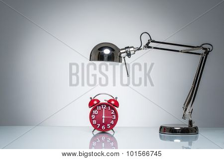 Lighting Up Red Alarm Clock With Desk Lamp