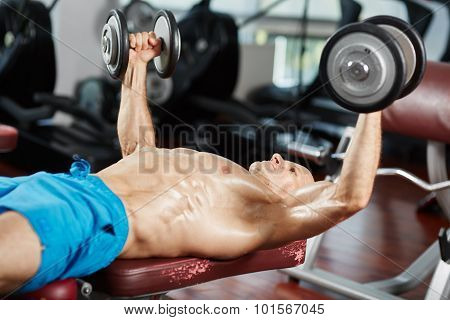 Young fit man working out at bench press with dumbbells poster