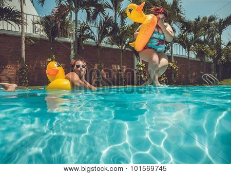 Beautiful young fat woman is jumping into the summer water pool with yellow duck   lifebuoy