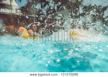 Girl with yellow duck lifebuoy with jumping splash into the summer water pool